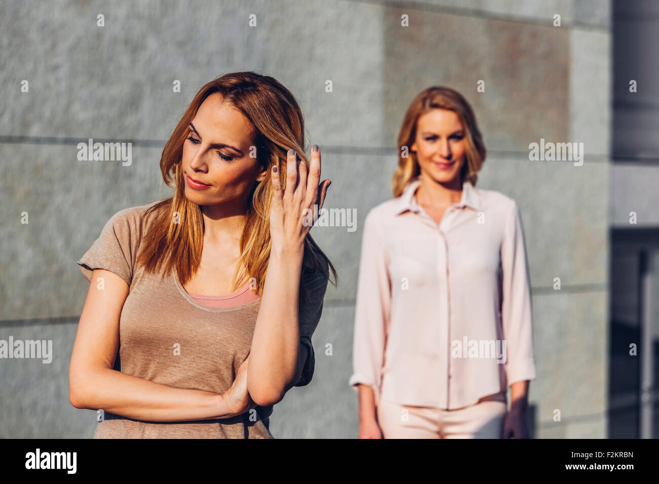 Serious blond woman outdoors with woman in background - Stock Image