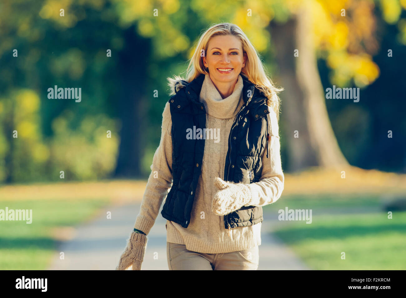 Portrait of smiling woman wearing warm clothes walking in a park - Stock Image