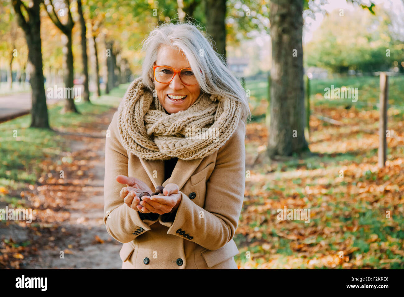 Portrait of woman wearing scarf holding something in her cupped hands - Stock Image