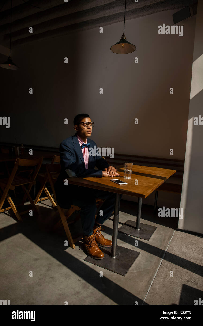 Young man sitting in cafe, waiting for someone, eyes closed - Stock Image