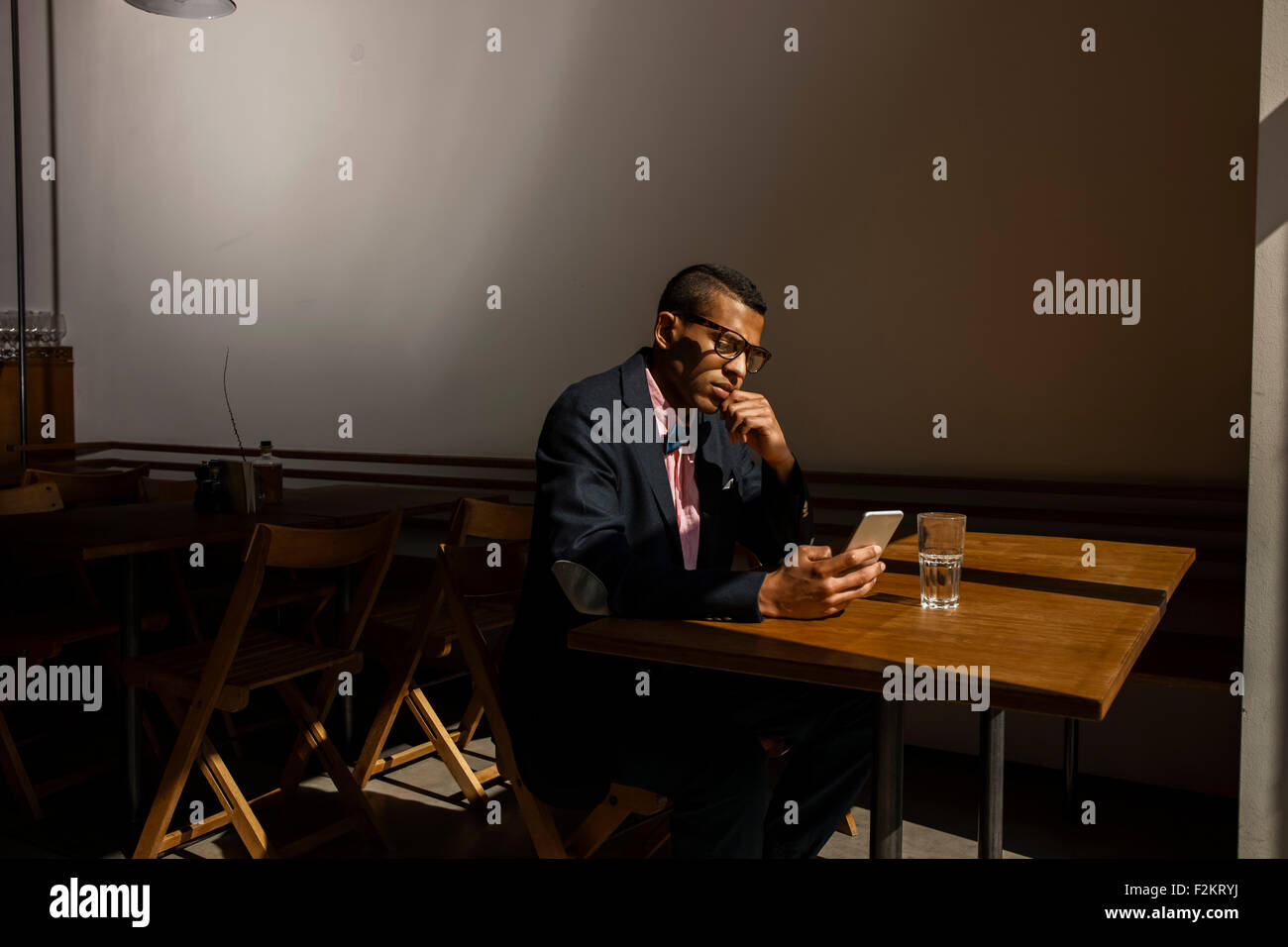 Young man sitting in cafe, waiting for someone, reading text message - Stock Image