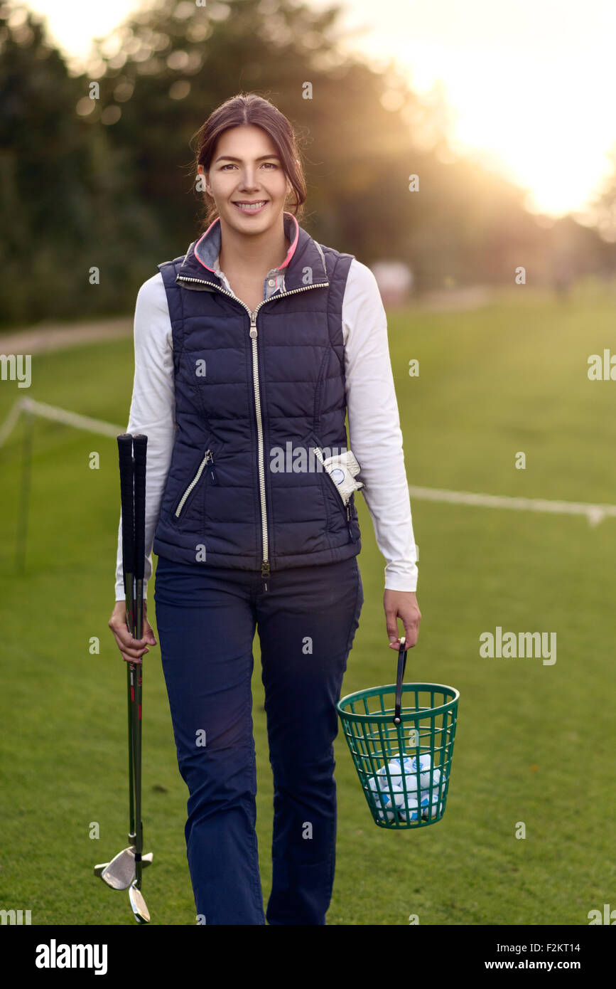 Smiling attractive woman golfer carrying balls in a plastic basket and her clubs on a driving range as she prepares Stock Photo