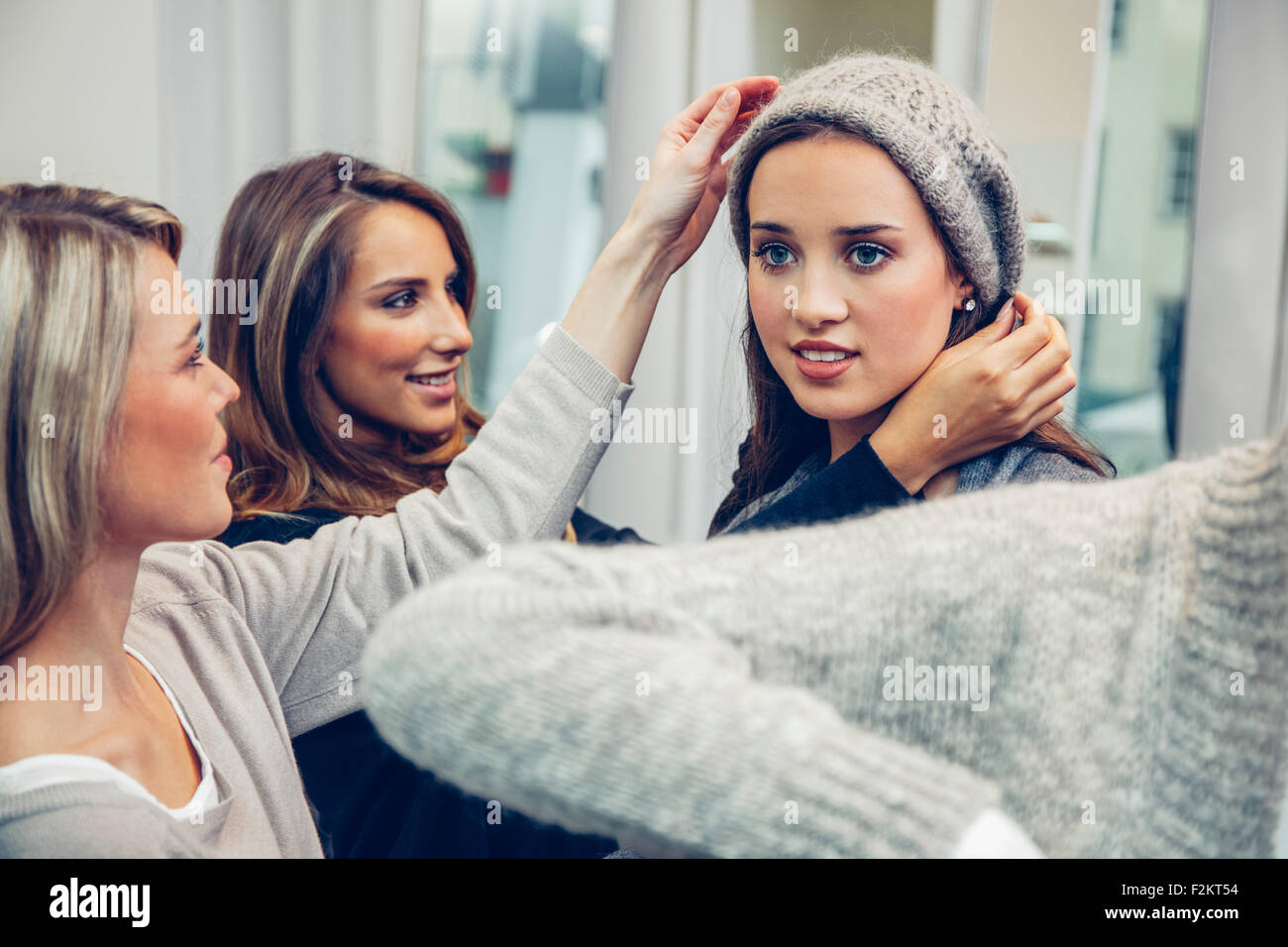 Young woman putting on woolly hat in a boutique assisted by two women - Stock Image