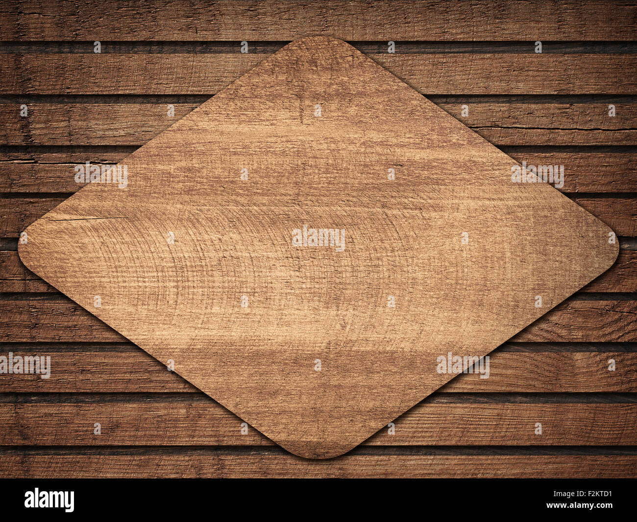 Brown wooden lozenge with shadow on planks wall - Stock Image