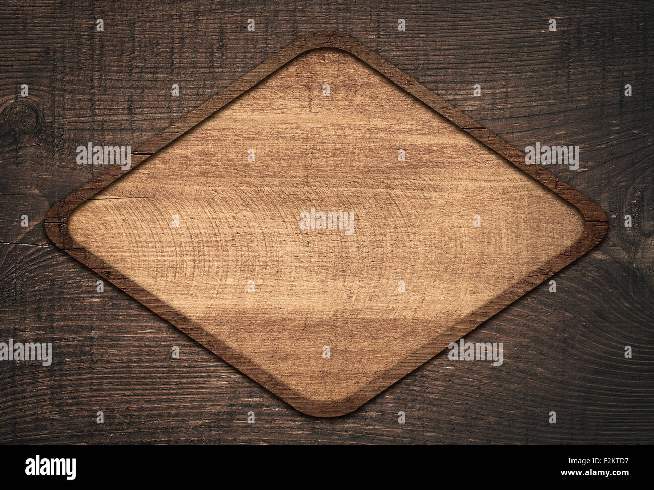 Brown wooden lozenge with frame on dark wall - Stock Image