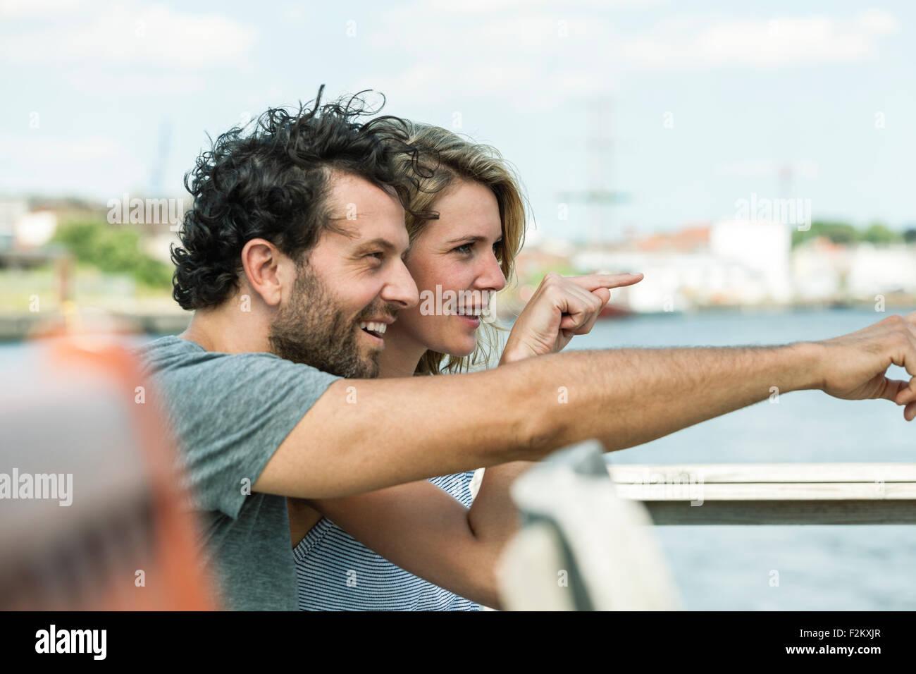 Germany, Luebeck, smiling couple pointing at something - Stock Image