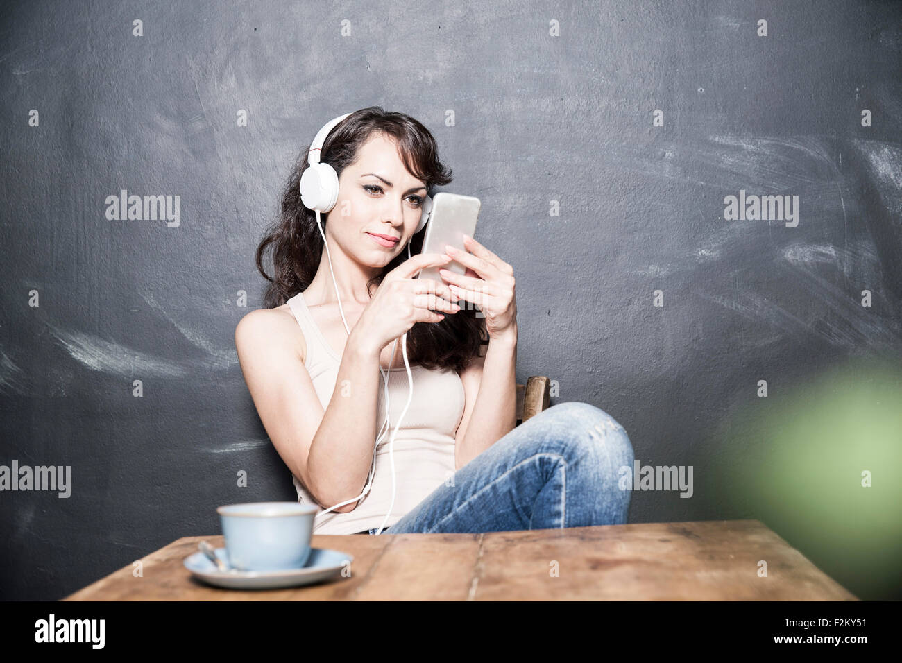 Dark haired businesswoman sitting at table, wearing headphones, using smart phone - Stock Image