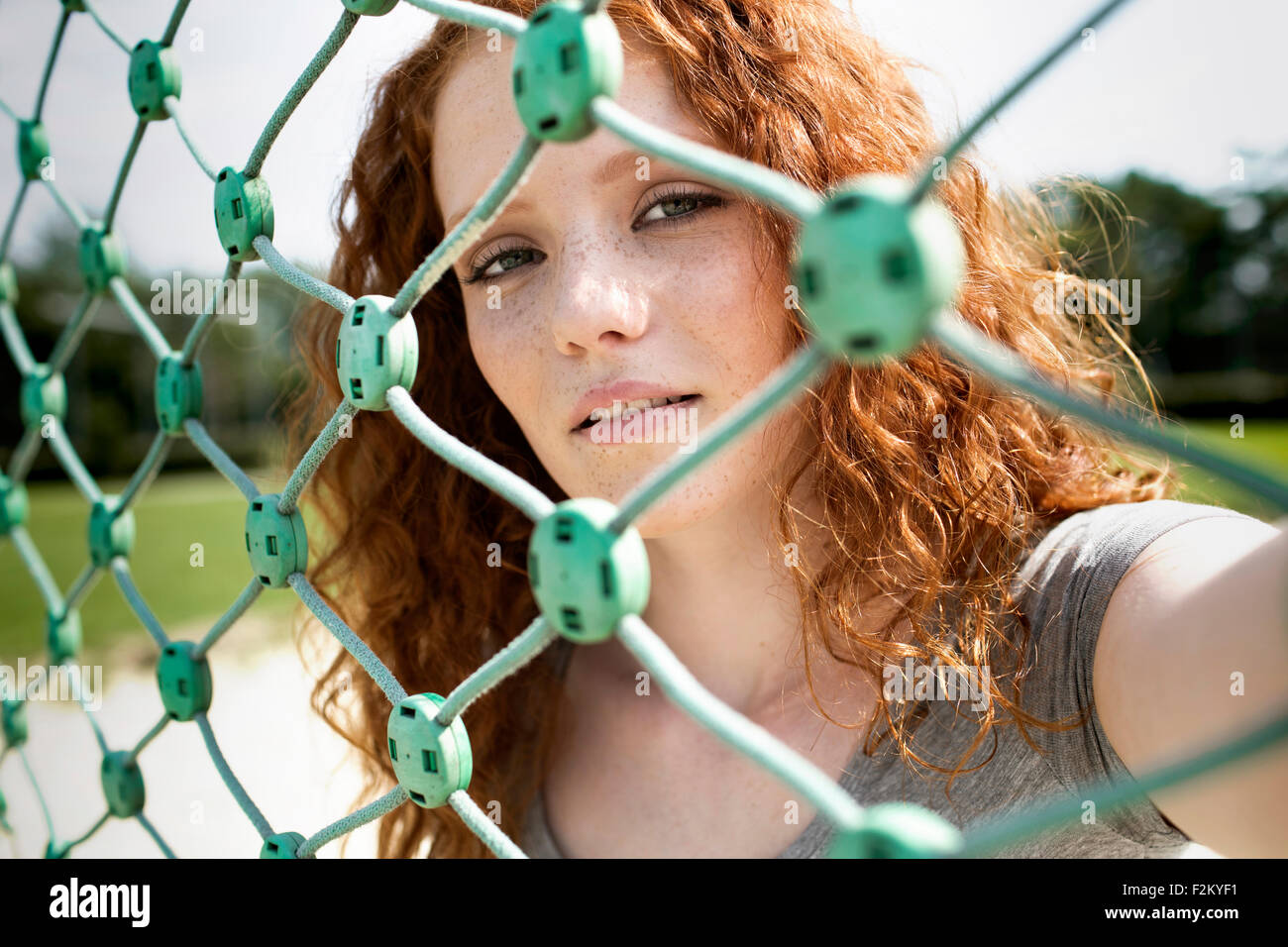 Portrait of redheaded teenage girl looking through net - Stock Image