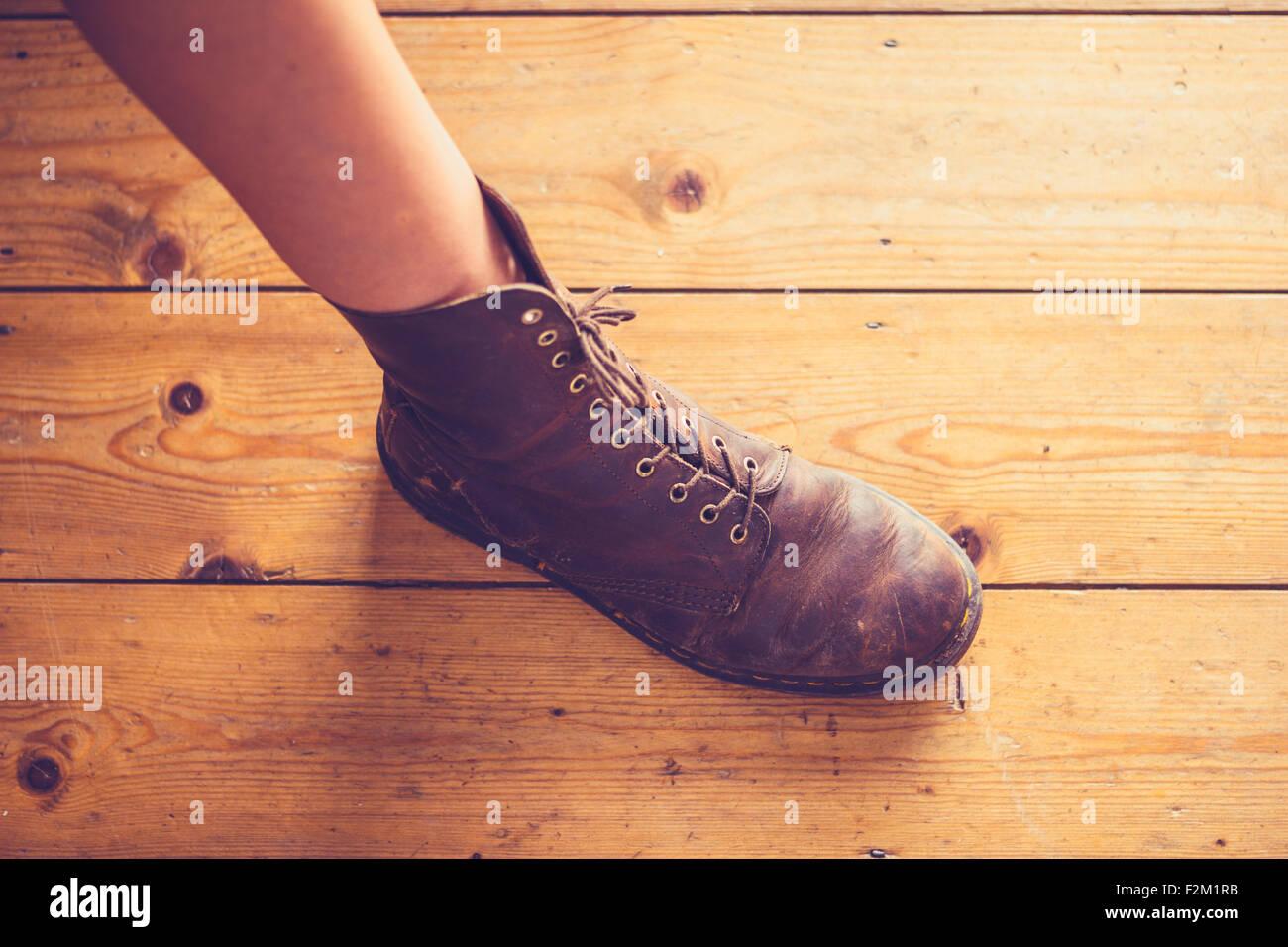 Woman's foot on wooden floor - Stock Image