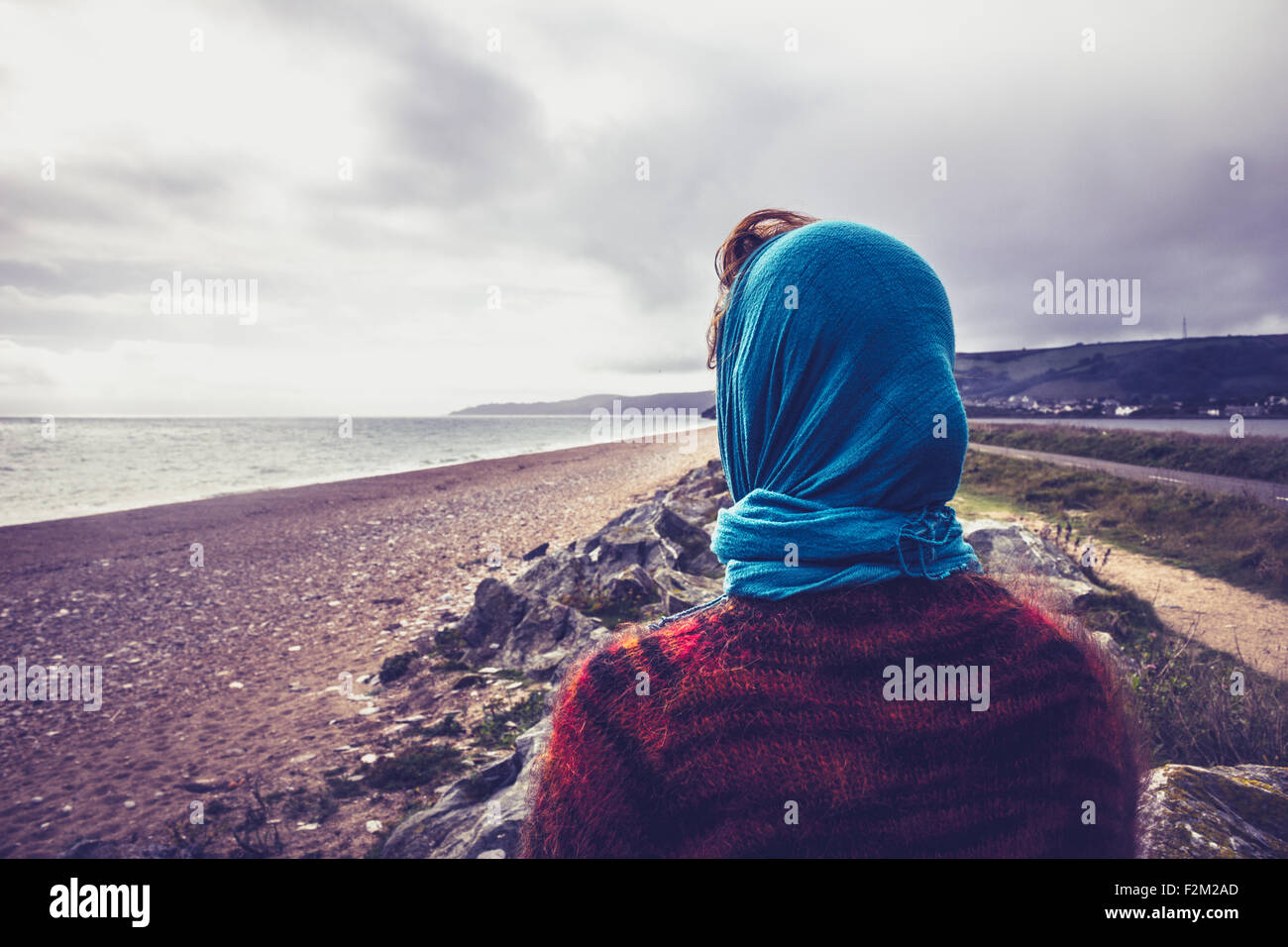 Young woman standing on beach in winter - Stock Image