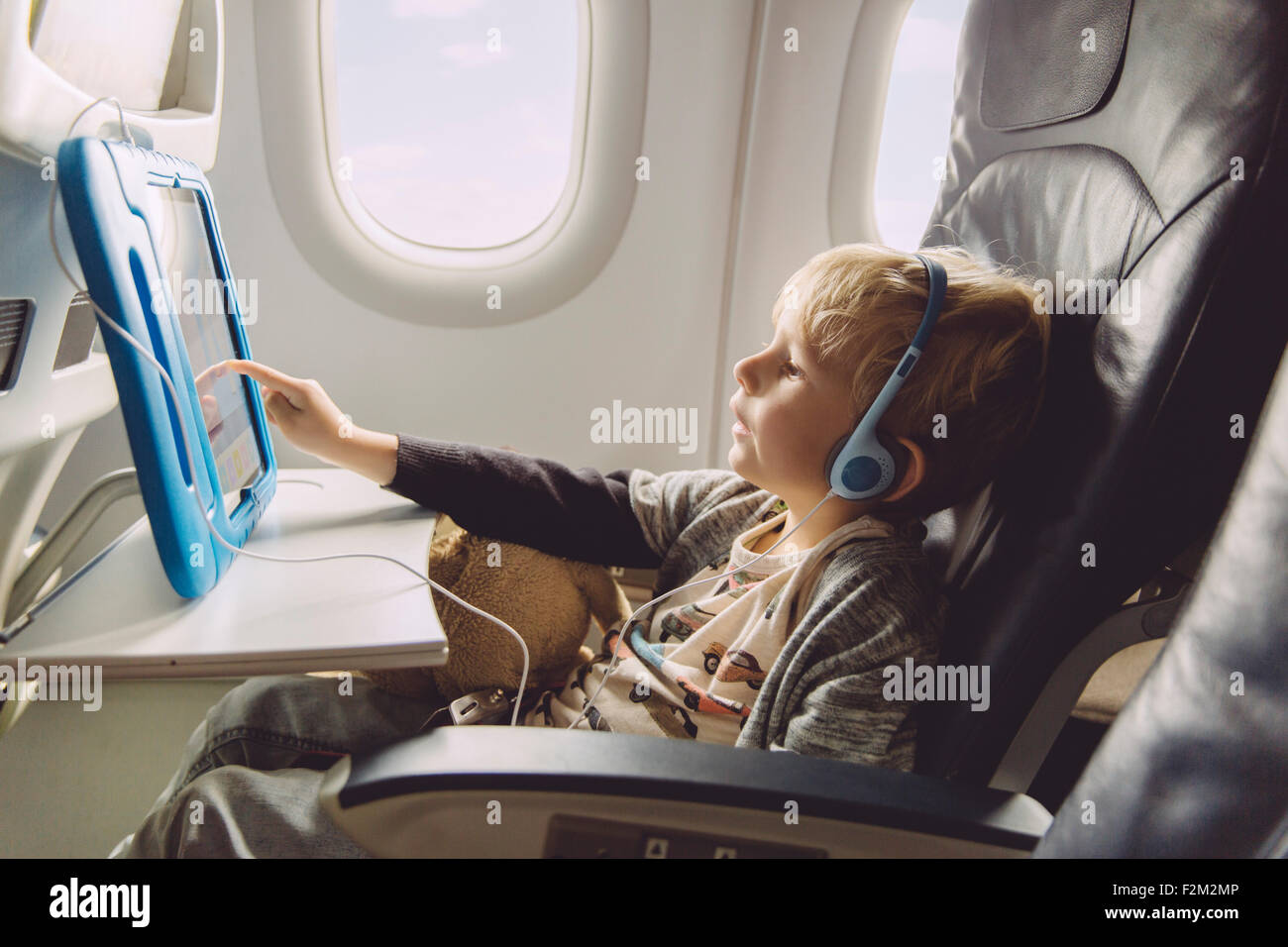 Little boy sitting on an airplane watching something on digital tablet - Stock Image