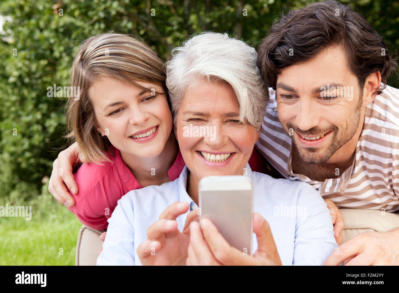 Mother with adult children looking at cell phone outdoors - Stock Image