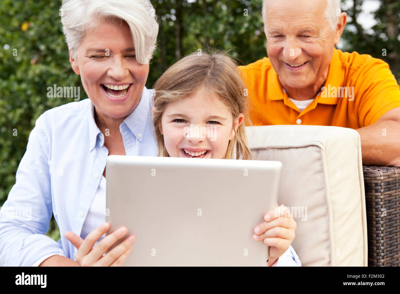Happy grandparents and girl outdoors using digital tablet - Stock Image