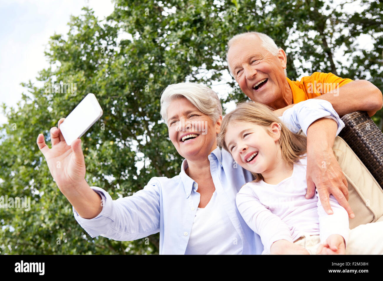 Happy grandparents and girl outdoors taking a cell phone picture - Stock Image