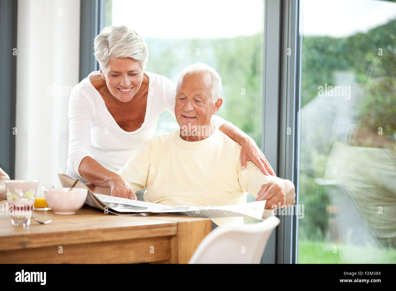 Mature couple reading newspaper at breakfast table - Stock Image