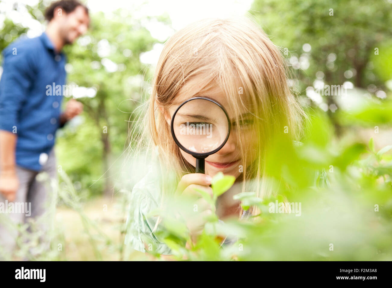 Girl in the nature looking through magnifying glass - Stock Image