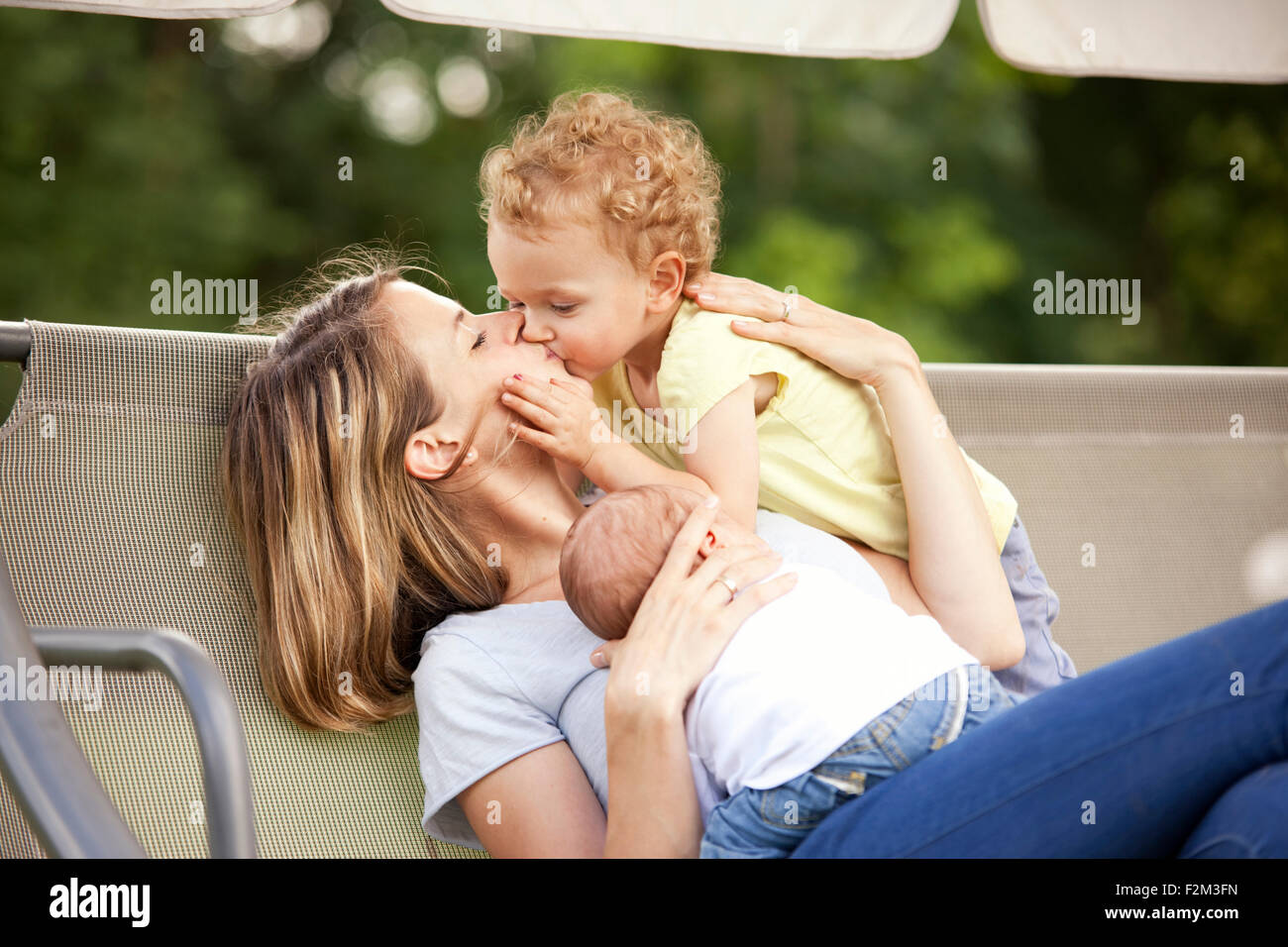 Young mother with her two little daughters on a canopy swing - Stock Image