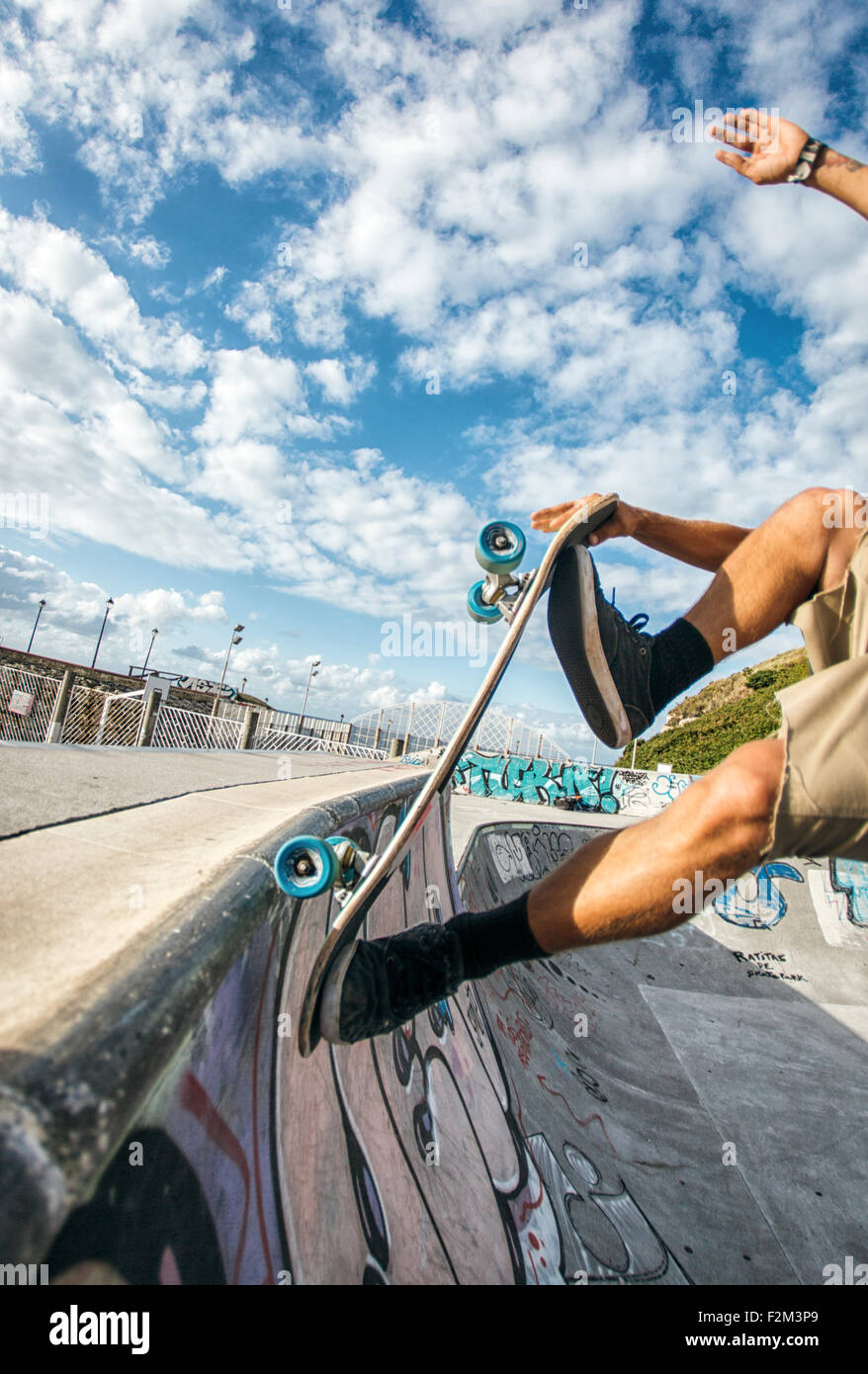 Legs of young man skateboarding in a skatepark - Stock Image