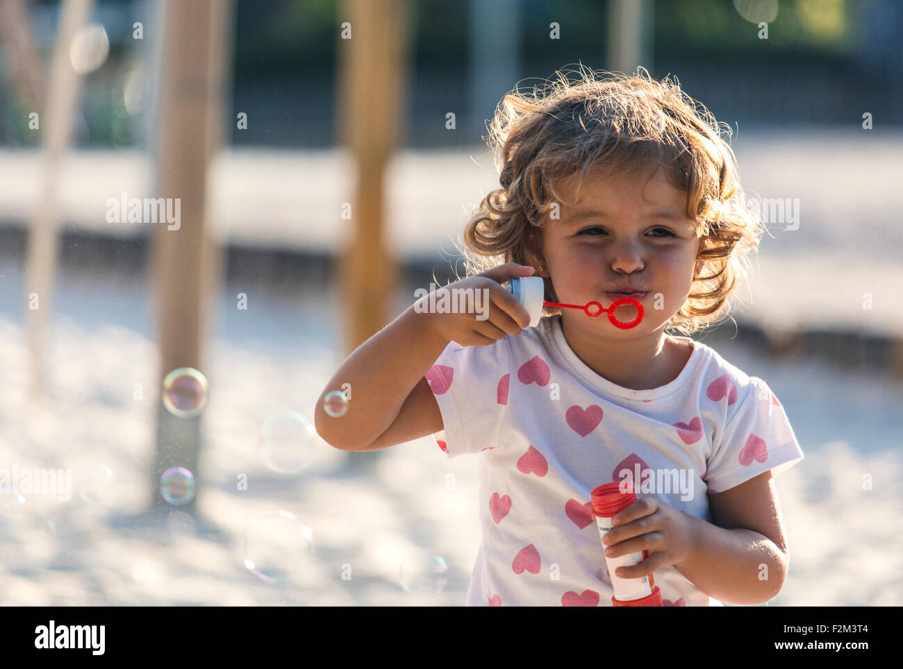 Little girl making soap bubbles at playground - Stock Image