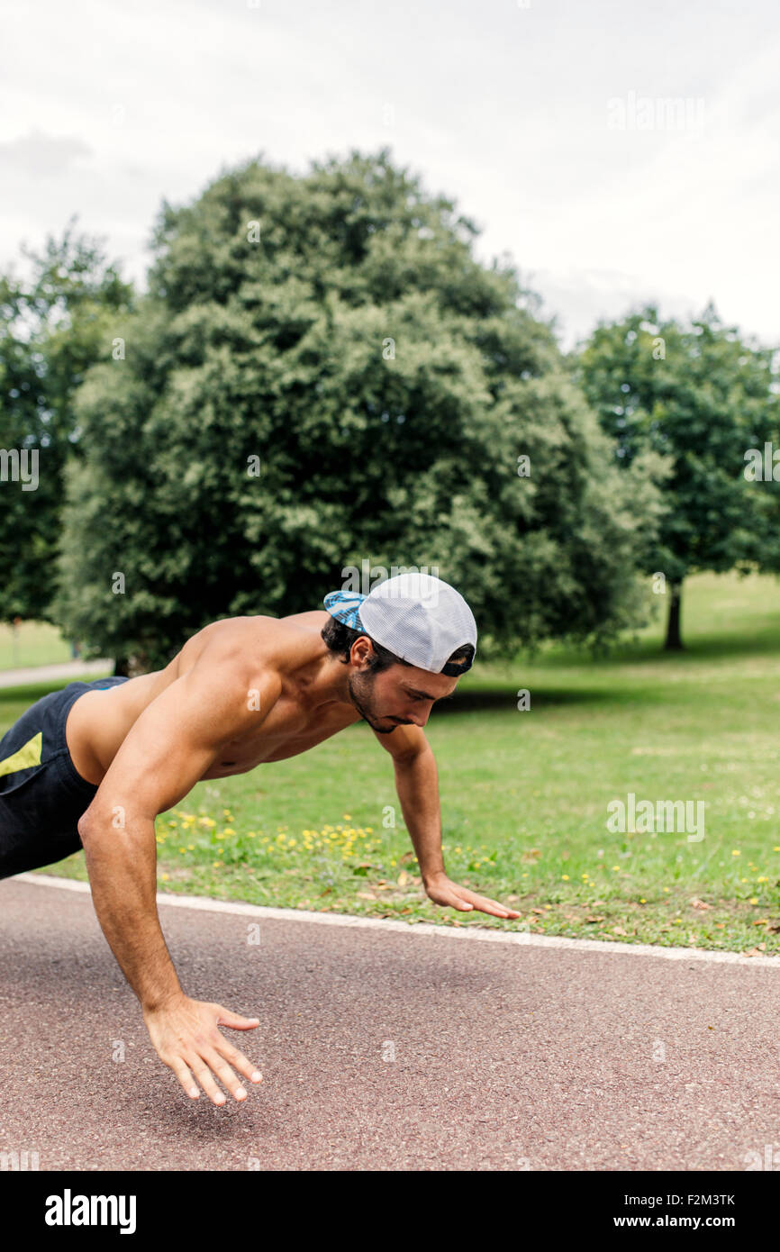 Athletic young man doing workout in the park - Stock Image
