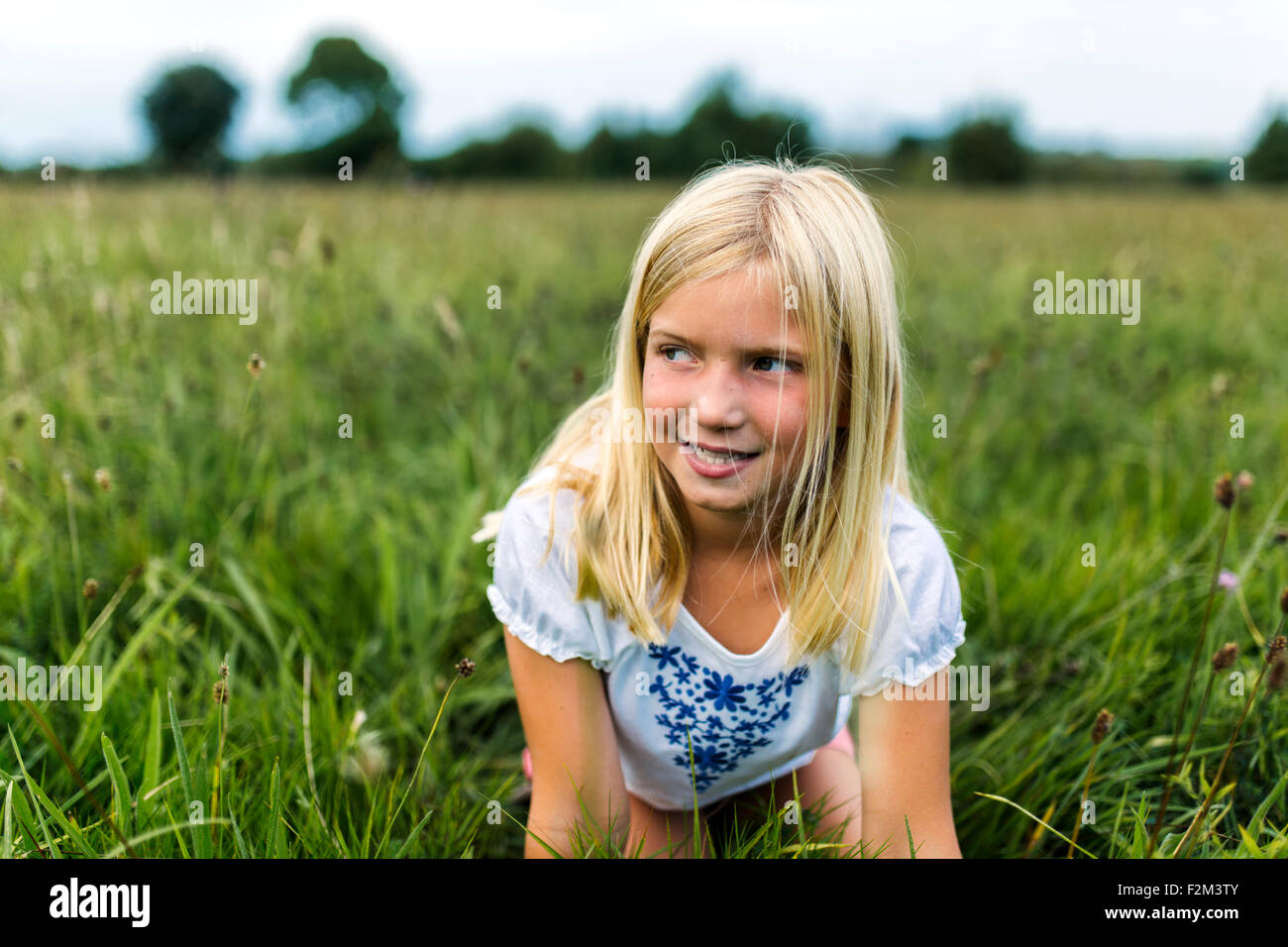 Portrait of girl kneeling on a meadow watching something - Stock Image
