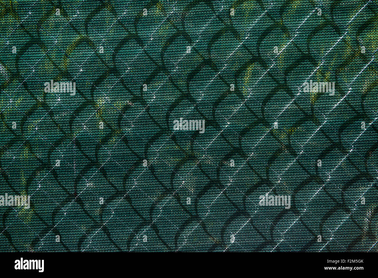 chain link fence shadow on plastic sheet at a construction site. - Stock Image