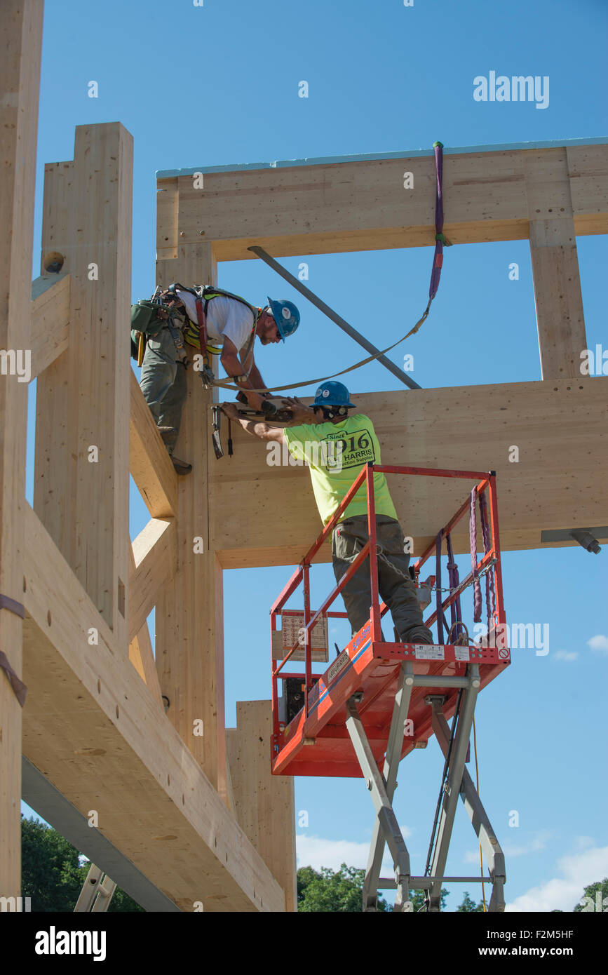 16,000 pound wooden engineered timber trusses await installation by crane for Leed Platinum Common Ground High School - Stock Image