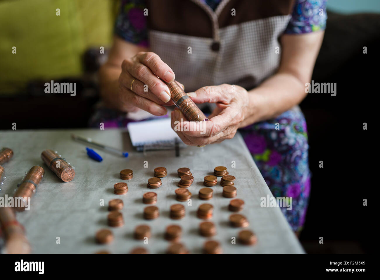 Elderly woman counting money, making stacks of Euro cents - Stock Image