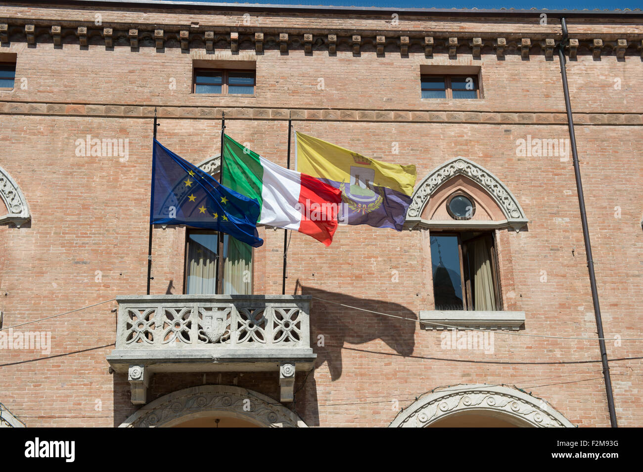 Local,country and European Union flags flutter on the town hall of Verucchio, Italy - Stock Image