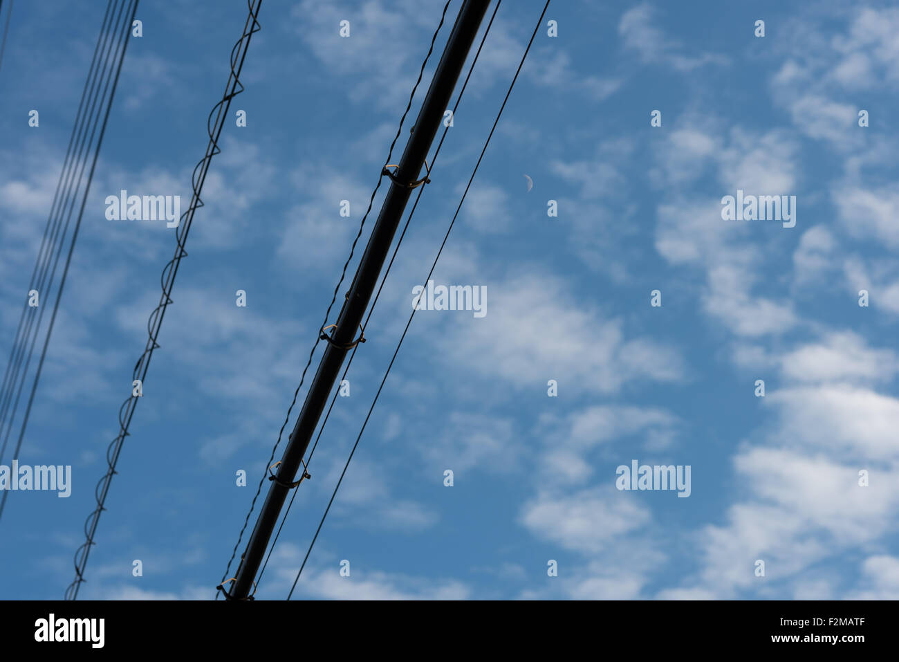 Black Power lines crossing a blue sky dappled with soft clouds and a cresent moon. - Stock Image
