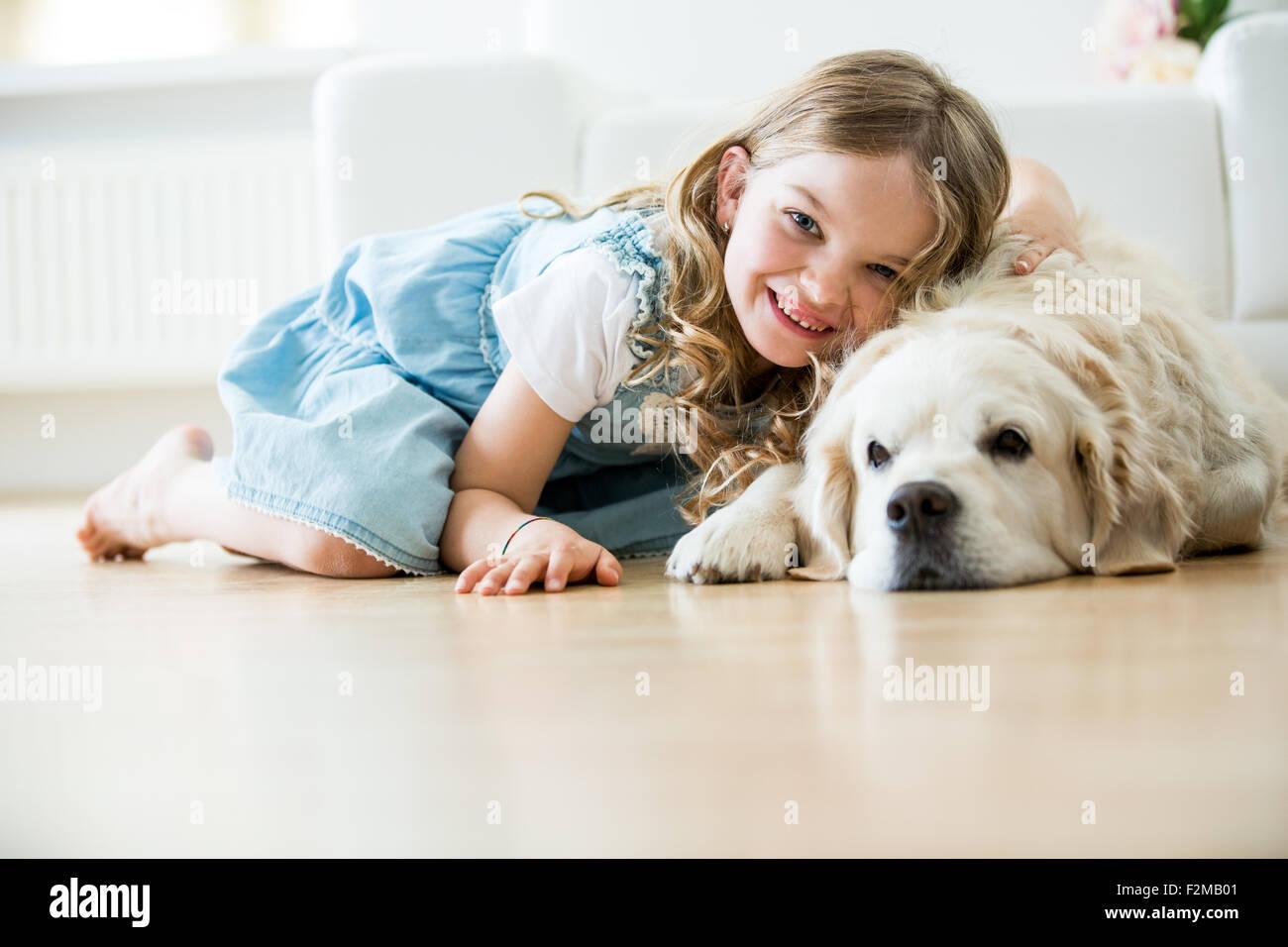 Little girl cuddling with her dog, lying on floor - Stock Image