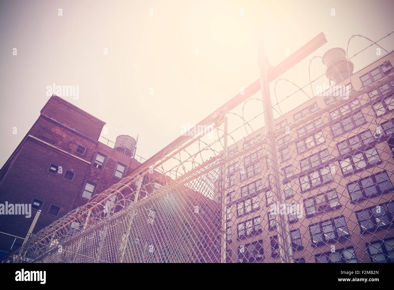 Retro toned old building protected with barbed wire fence, New York, USA. - Stock Image