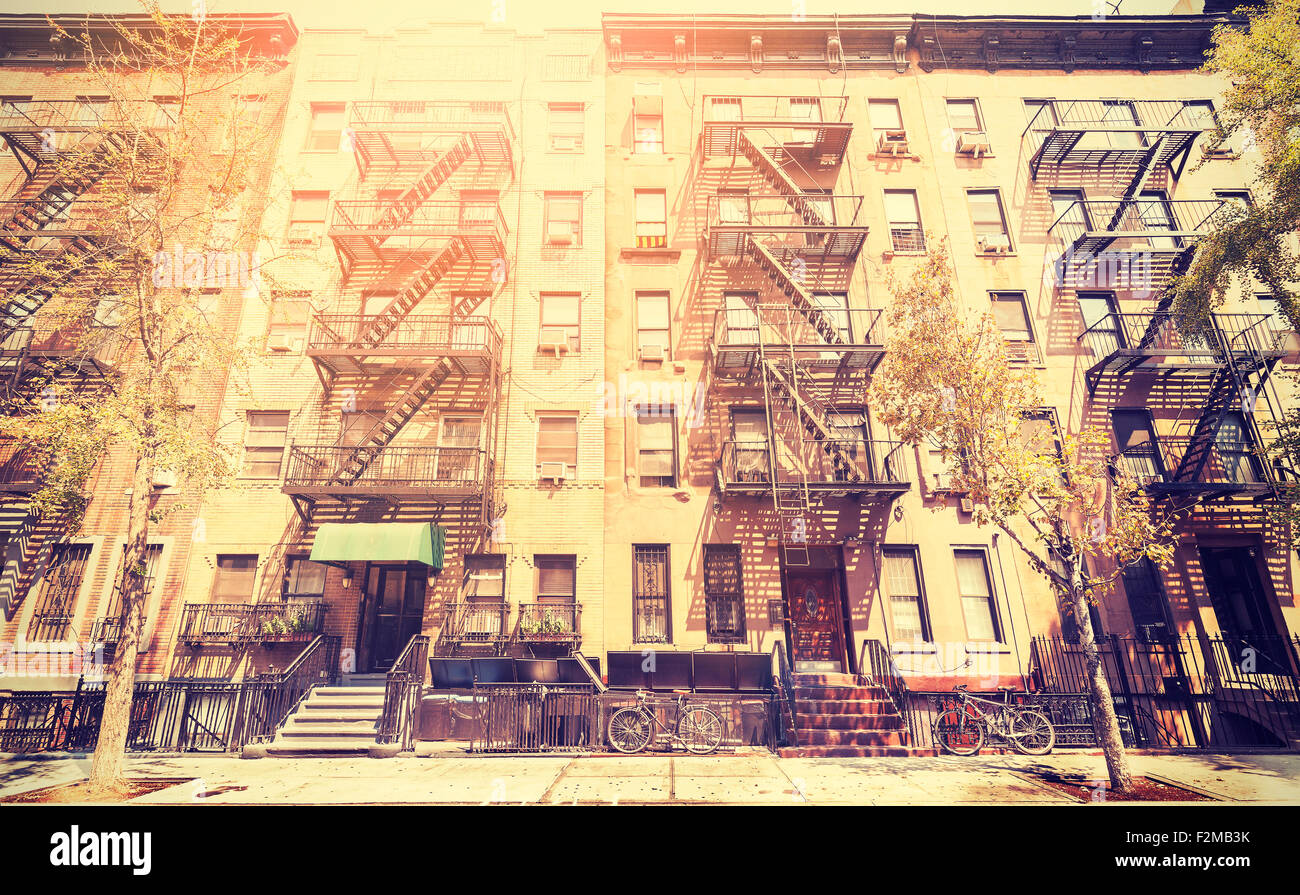 Old film retro style photo of New York building with fire escape ladders, USA. - Stock Image