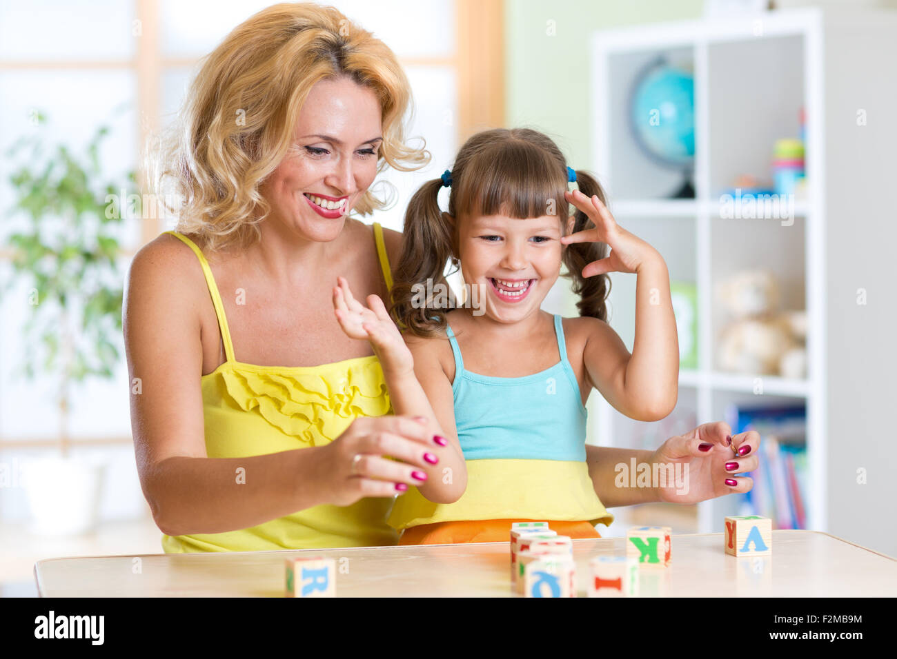 Happy family plays in home interior - Stock Image
