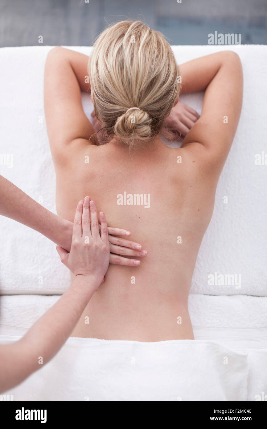 Young woman getting a back massage in a spa - Stock Image
