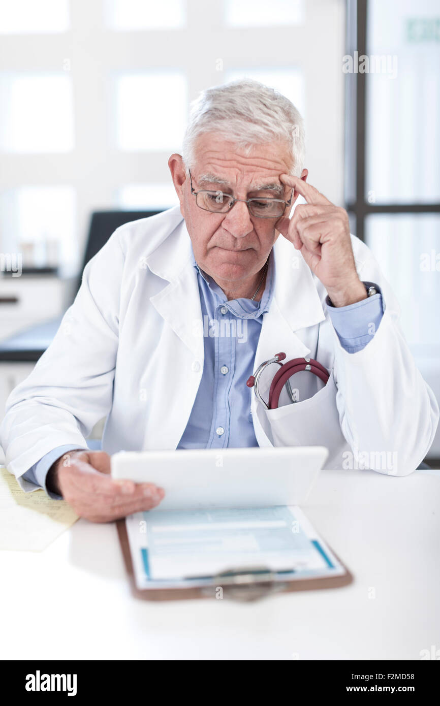 Serious senior doctor at desk looking at patient file - Stock Image