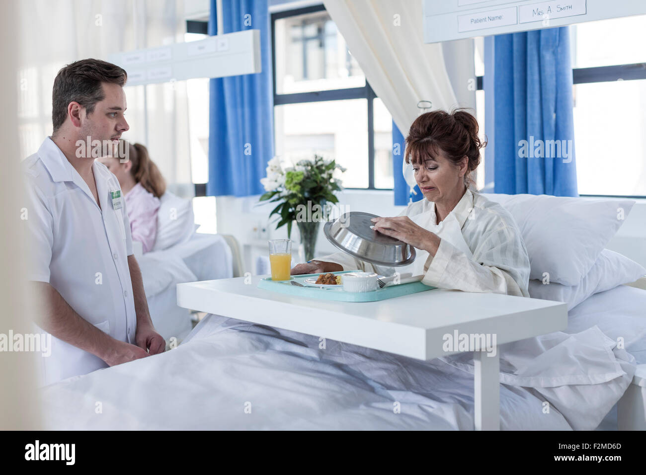 Nurse looking at skeptical patient receiving lunch - Stock Image