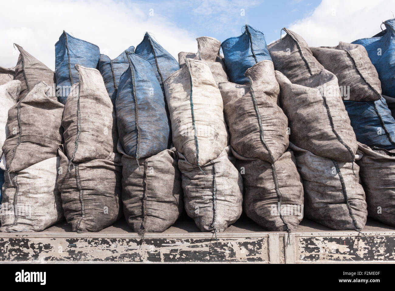 Piled-up coal sacks on the back of a flat-back lorry. - Stock Image