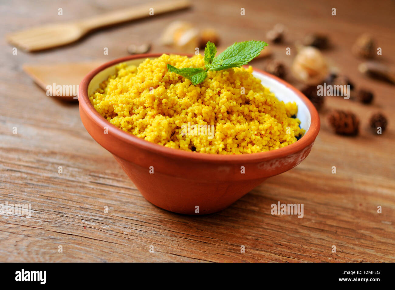 an earthenware bowl whit spiced couscous on a rustic wooden table - Stock Image