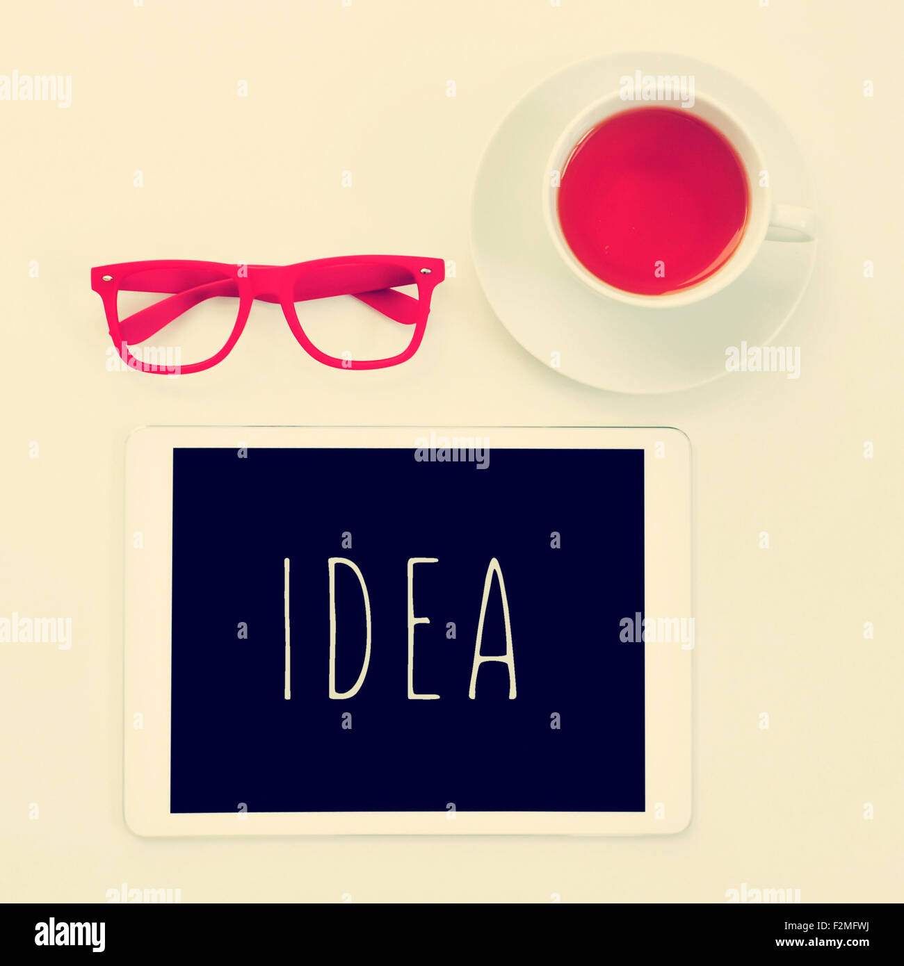 high-angle shot of a table with a pair of red plastic-rimmed eyeglasses, a cup of tea and a tablet computer with - Stock Image