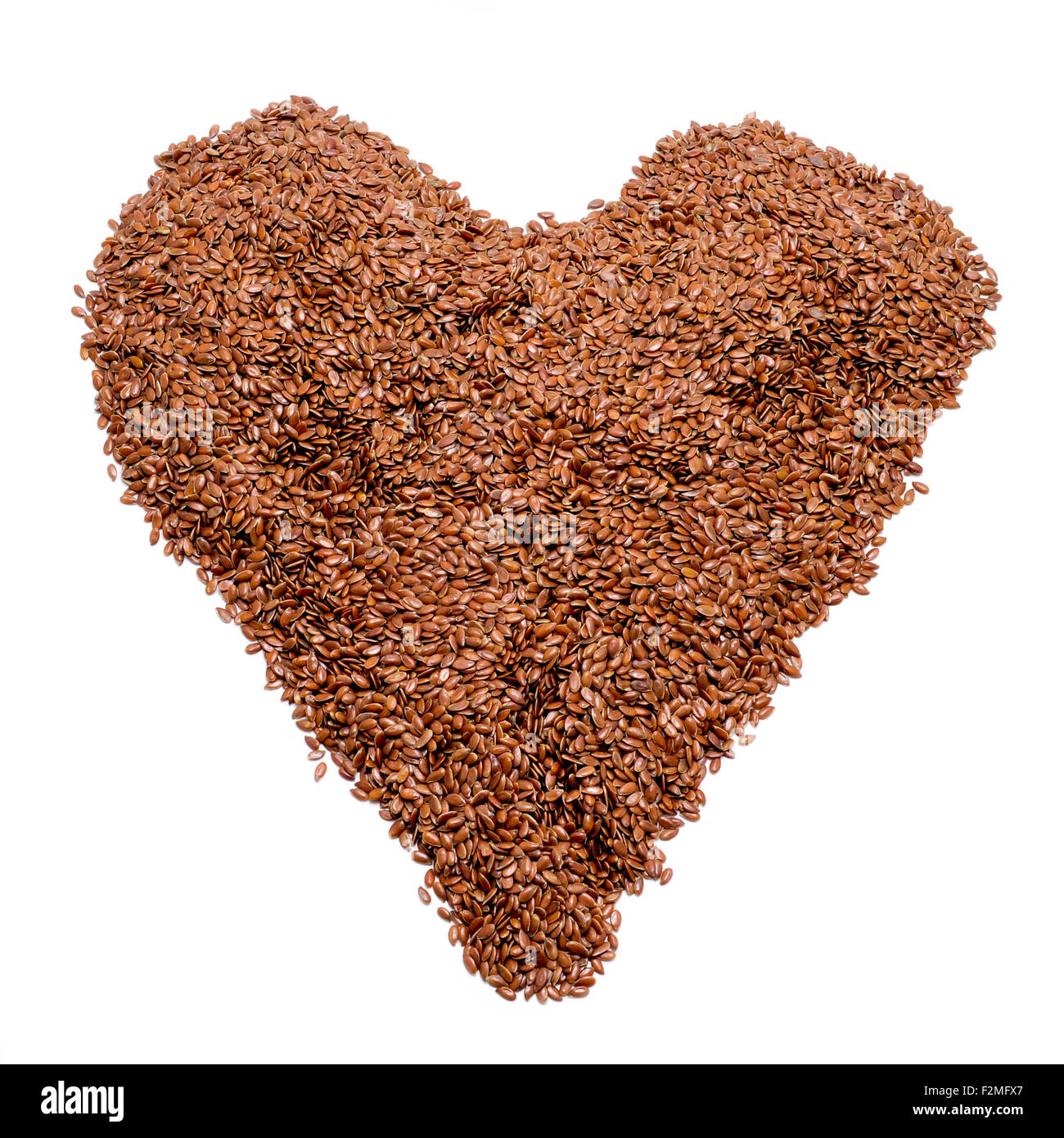 a pile of brown flax seeds forming a heart on a white background - Stock Image