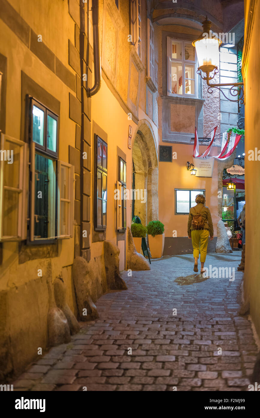 Woman traveler traveller alone alley Europe. A female traveller walks along an alley leading to the historic centre - Stock Image