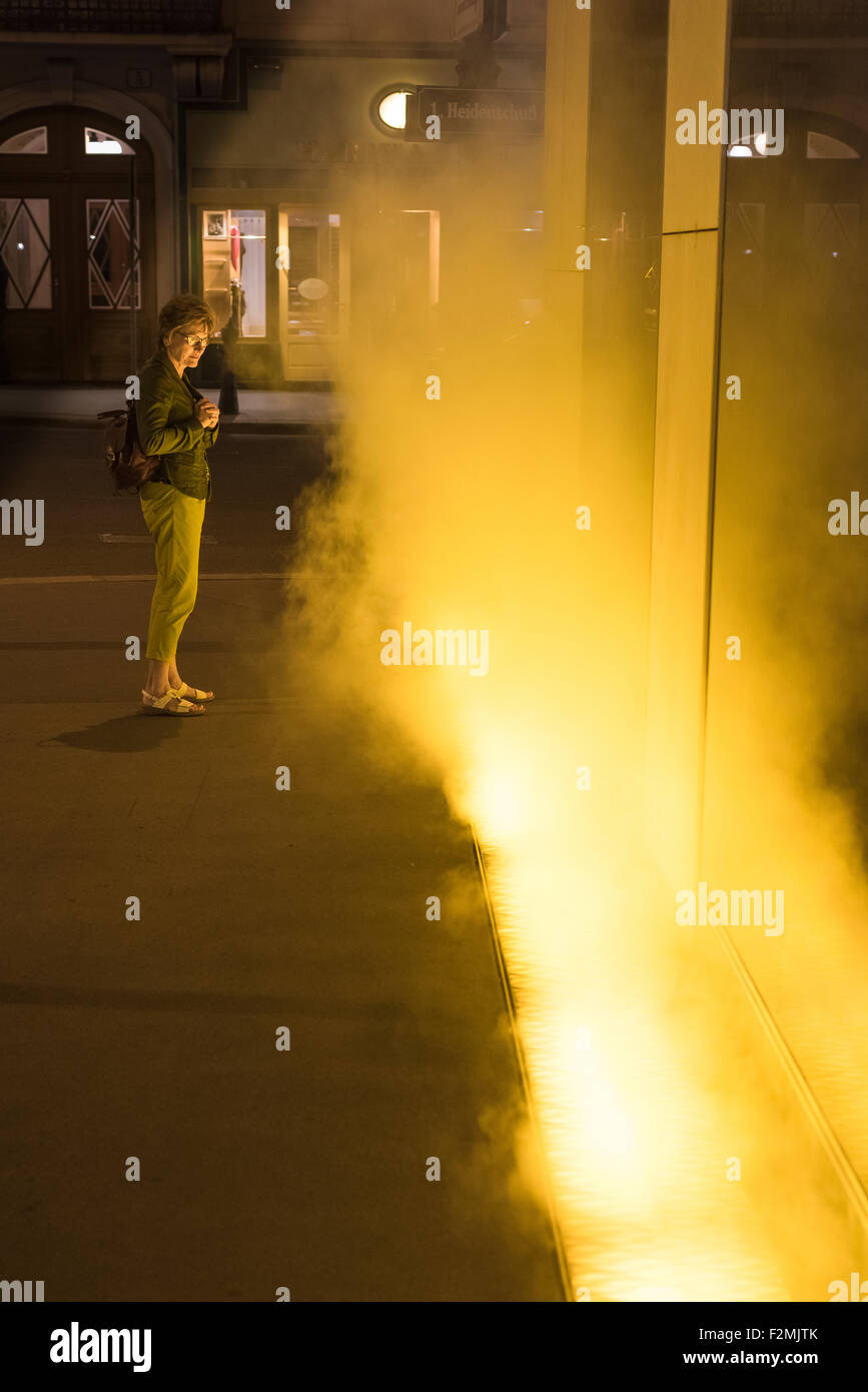 Yellow fog Olafur Eliasson. A woman passerby in Vienna pauses to watch a public installation designed by Olafur - Stock Image