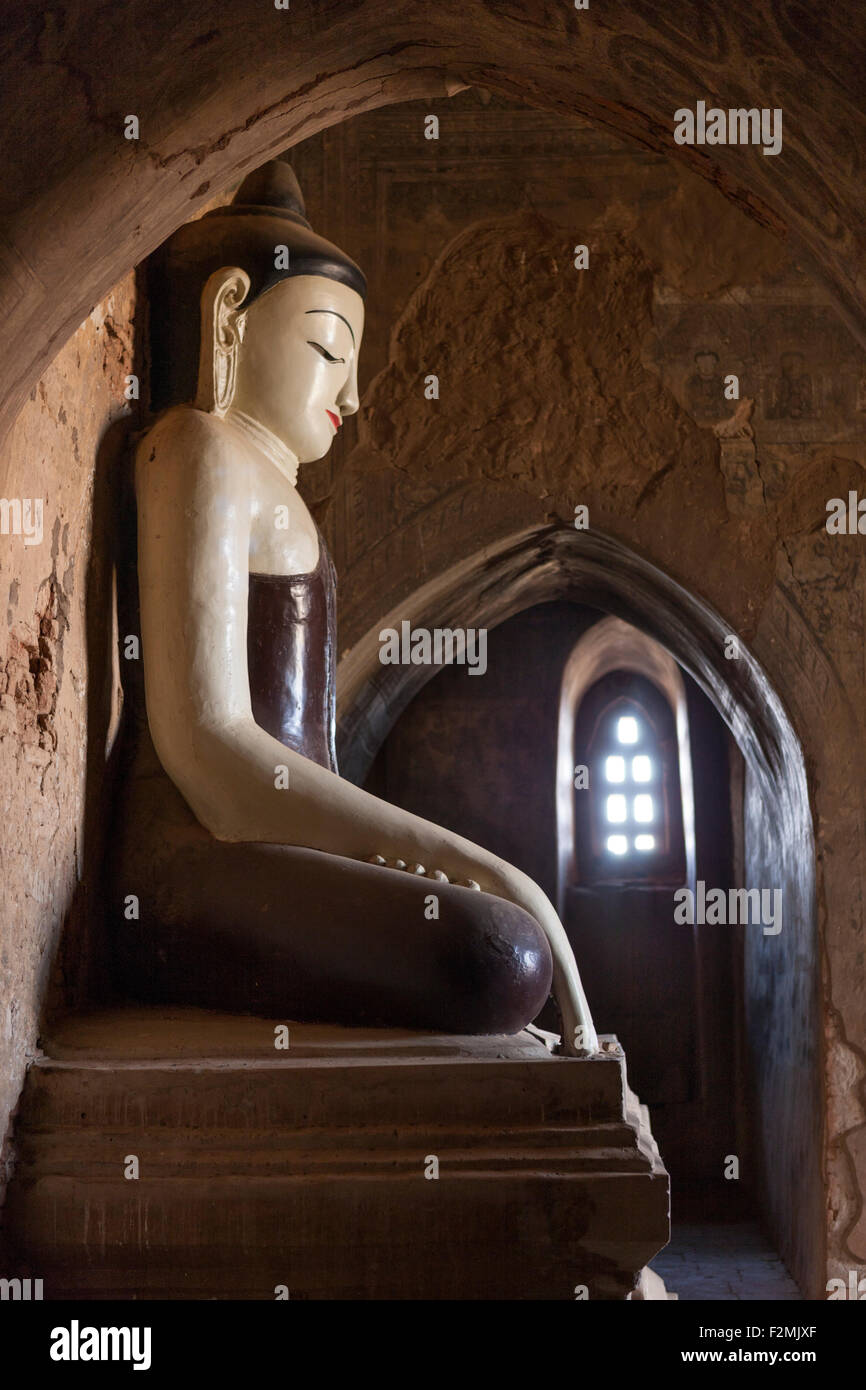 Side view of Buddha statue, 12th century Tayok Pye Pahto (Pagoda) at Bagan Myanmar. Remnants of color frescoes visible - Stock Image