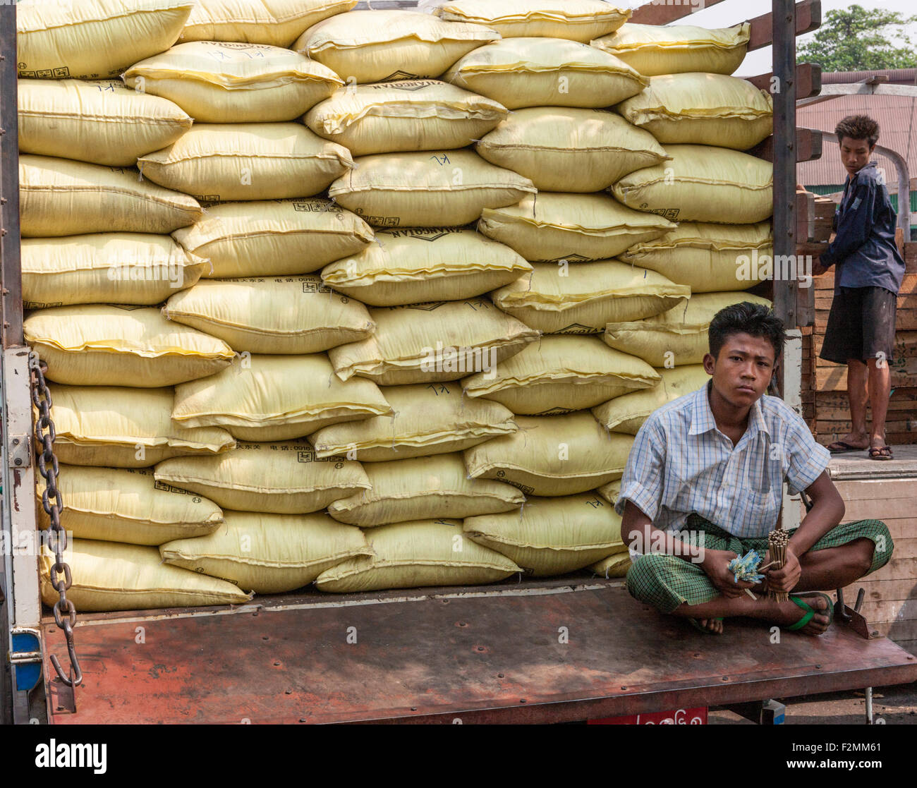 Truck full of rice sacks at Port of Yangon with longshoreman sitting on tailgate holding tally sticks - Stock Image