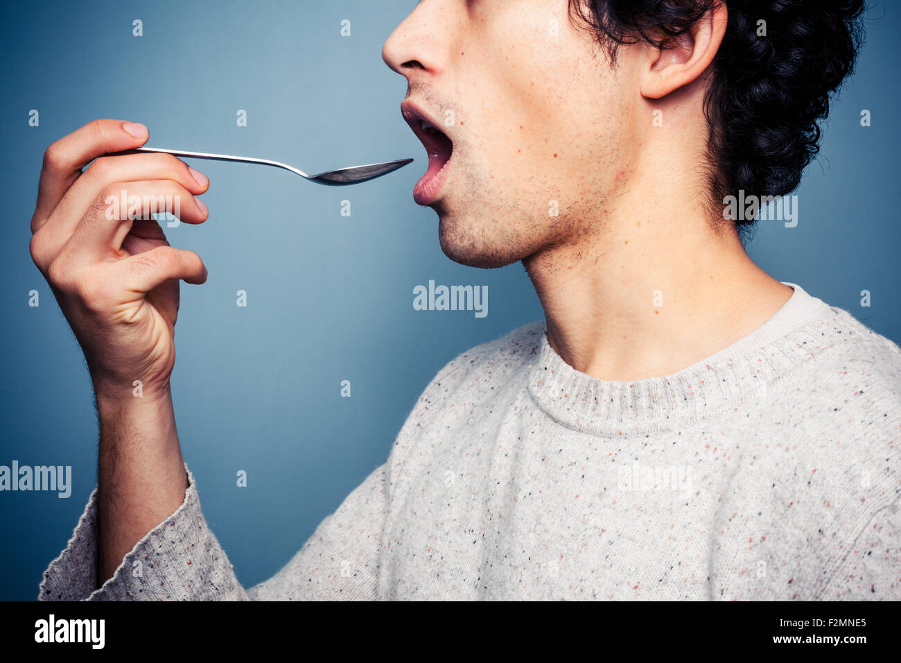 Young man putting spoon in his mouth - Stock Image