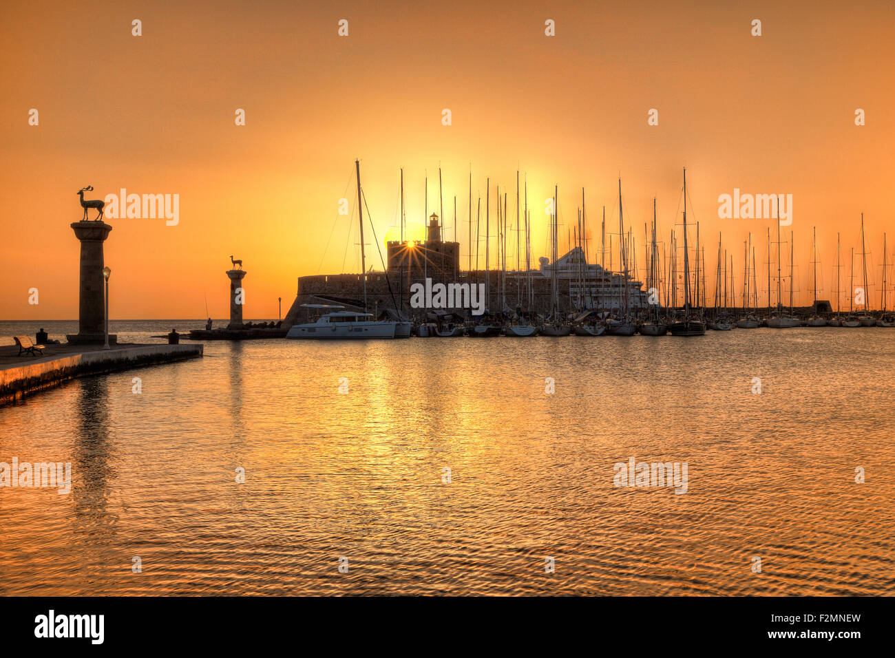 The sunrise at the entrance with the deers of the old port of Rhodes, Greece - Stock Image