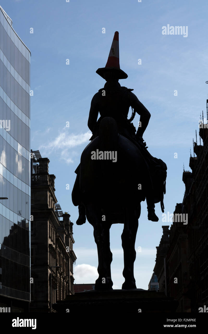 Silhouette of the Duke of Wellington statue wearing a cone on its head in Glasgow city centre, Scotland, UK - Stock Image