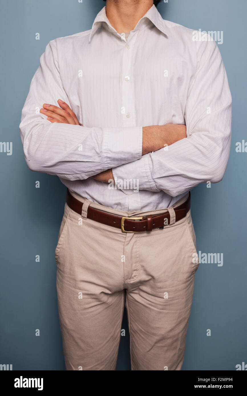 Young man standing by a blue wall with arms crossed - Stock Image