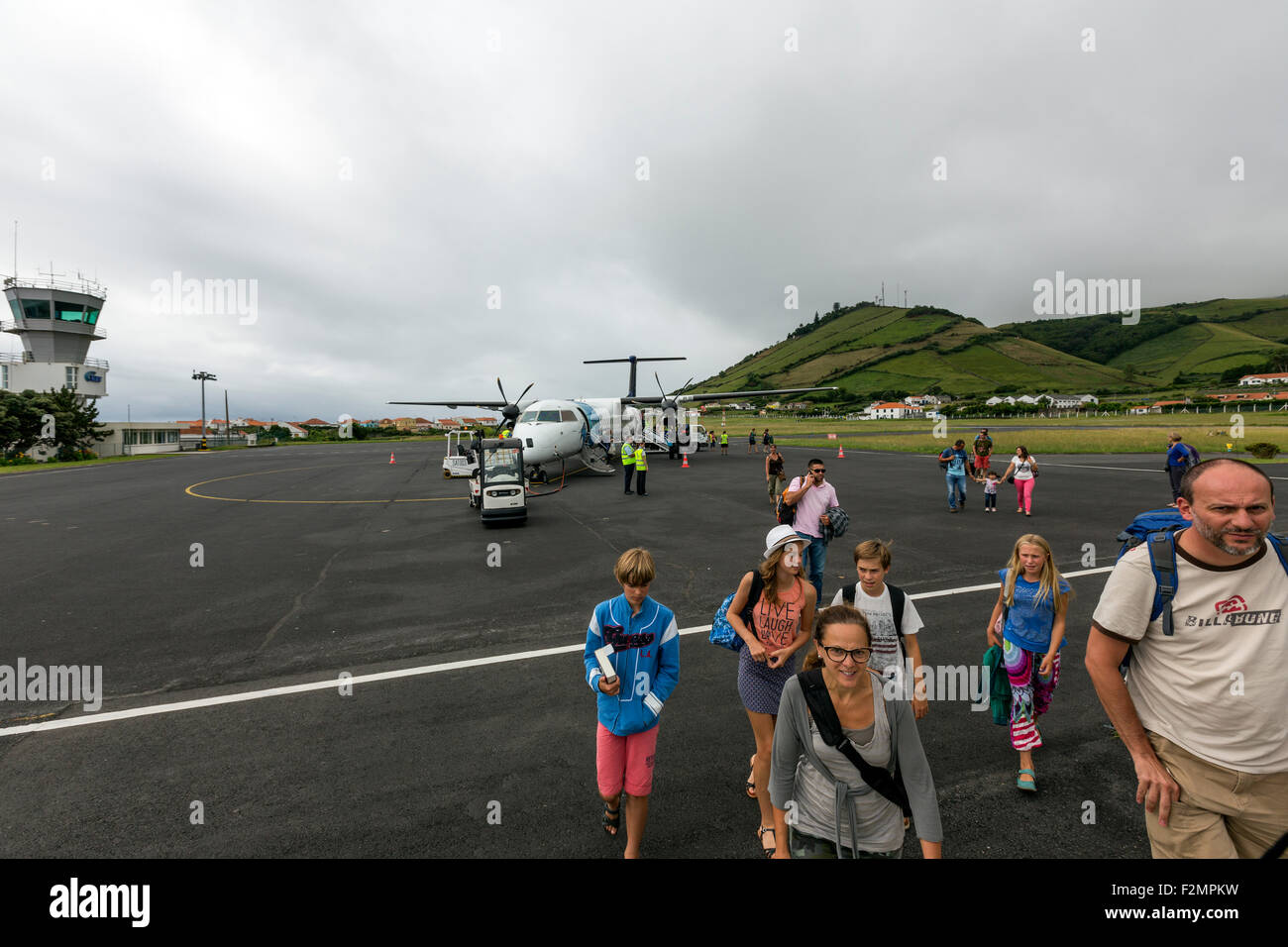 Tourist people walking to the Santa Cruz airport terminal the De Havilland DHC-8-400 Dash 8Q from Ponta Delgada - Stock Image